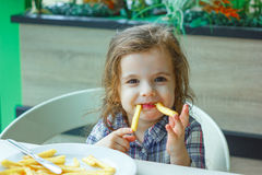 Little girl play with the french fries in a restaurant. Royalty Free Stock Photo