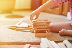 Little girl play game on carpet and builds tower, development toys, light effect royalty free stock photos