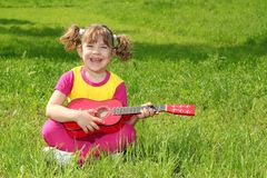 Little girl play guitar Stock Photo