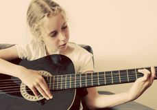 Little girl play guitar. Royalty Free Stock Images