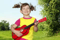 Little girl play guitar outdoor Stock Photos
