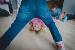 Little girl play home while father is doing homework with son. Difficult parenting stock photography
