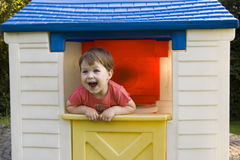 Little Girl In Play House. Two year old happy girl looking through the window of her cubby house, laughing Stock Photography