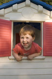 Little Girl In Play House. Two year old happy girl looking through the window of her cubby house, laughing Royalty Free Stock Images