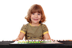 Little girl play music on keyboard Stock Images