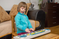 Little girl play music on keyboard Stock Photos