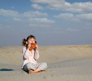 Little girl play music on pan pipe Royalty Free Stock Photo