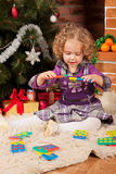 Little girl play near Christmas tree Royalty Free Stock Images