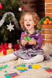 Little girl play near Christmas tree Royalty Free Stock Photos