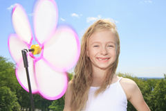 Little girl play outside with a wind flower Stock Photos