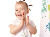 Little girl play with paints, clapping her hands Royalty Free Stock Images