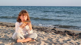 Little girl play pan pipe Stock Photo