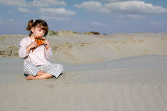 Little girl play panpipe in desert Royalty Free Stock Photo