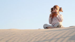 Little girl play panpipe in desert Royalty Free Stock Images