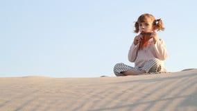 Little girl play panpipe in desert stock video