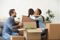 Little girl play with parents unpacking on moving day. Cute little girl child hide in cardboard box playing with young parents laughing together unpacking on royalty free stock image