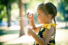 Little girl play in park blow soap bubbles profile close up. Cute little girl play in park blow soap bubbles profile close up summer day Royalty Free Stock Images