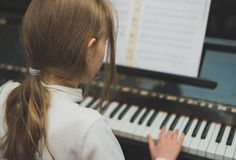Little girl play the piano royalty free stock photos