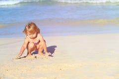 Little girl play with sand on beach. Cute little girl play with sand on beach Royalty Free Stock Photos