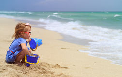 Little girl play with sand on beach. Cute little girl play with sand on beach Royalty Free Stock Images