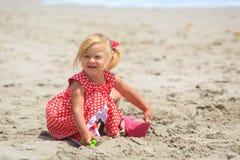 Little girl play with sand on beach. Cute little girl play with sand on beach Stock Image