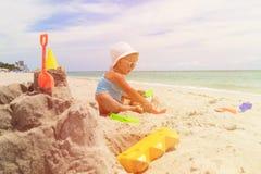 Little girl play with sand on beach. Cute little girl play with sand on beach Royalty Free Stock Image