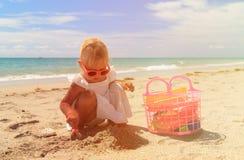 Little girl play with sand on beach. Cute little girl play with sand on beach Stock Images
