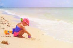 Little girl play with sand on beach. Cute little girl play with sand on summer beach Stock Photography