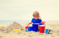 Little girl play with sand on beach. Family vacation Royalty Free Stock Photography