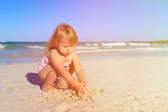 Little girl play with sand on beach. Family vacation Stock Photo