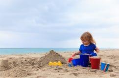 Little girl play with sand on beach. Family vacation Stock Photos