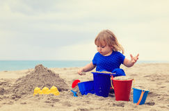 Little girl play with sand on beach. Family vacation Stock Photography