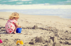 Little girl play with sand on beach. Family vacation Royalty Free Stock Image