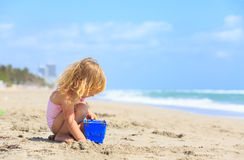 Little girl play with sand on beach. Family vacation Stock Images