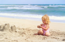 Little girl play with sand on beach. Family vacation Stock Image