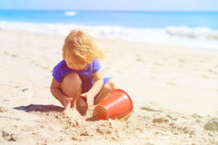 Little girl play with sand on beach. Family vacation Royalty Free Stock Photo