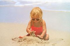 Little girl play with sand on beach. Family vacation Royalty Free Stock Images
