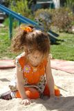 Little girl play in sandbox. At sunny day Stock Image