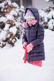 Little girl play with snow shoveling on a winter Royalty Free Stock Image