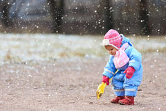 Little girl play in snow winter park Stock Photos