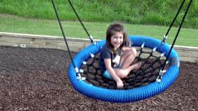 Little girl play on a swing in playground stock video footage