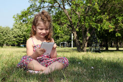 Little girl play with tablet Royalty Free Stock Images