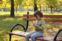 Little girl play with tablet in park Stock Photos