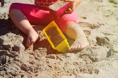 Little girl play with toys on beach Stock Photography