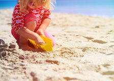 Little girl play with toys on beach Stock Images