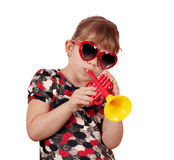 Little girl with play trumpet Royalty Free Stock Images
