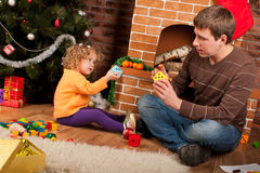 Little Girl Play With Dad Near Christmas Tree Stock Photo