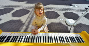 Little girl play yellow piano Royalty Free Stock Photo