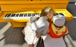 Little girl play yellow piano Stock Images