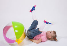 Little girl played with a ball and fell. On the floor Royalty Free Stock Photos